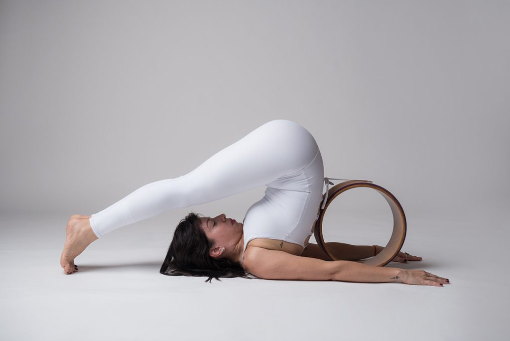 Jal Instructor Loli doing a Plow Pose (Halasana) with the help of Yoga Wheel