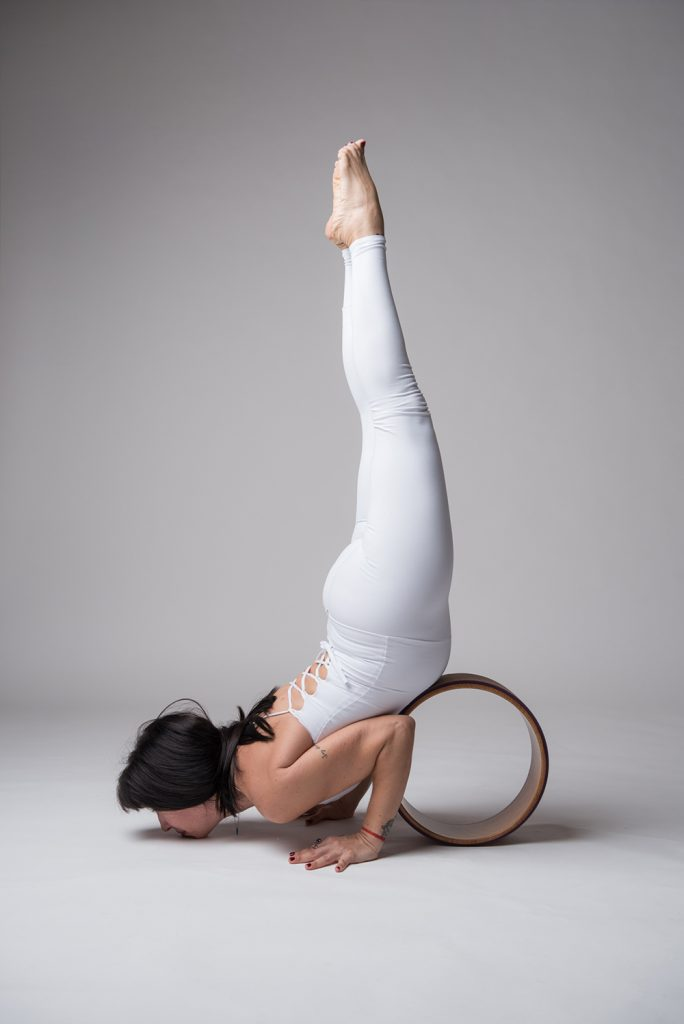 Wheel Yoga Teacher Loli doing a chin stand with the help with yoga wheel
